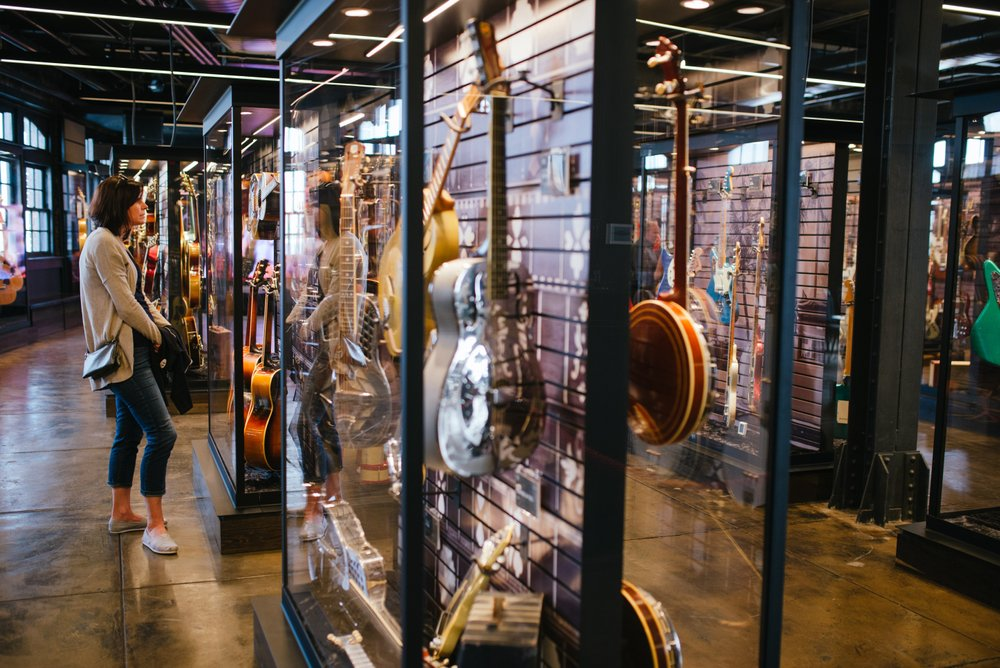 Songbirds Guitar Museum exhibit with guitars in glass cases and woman looking at them
