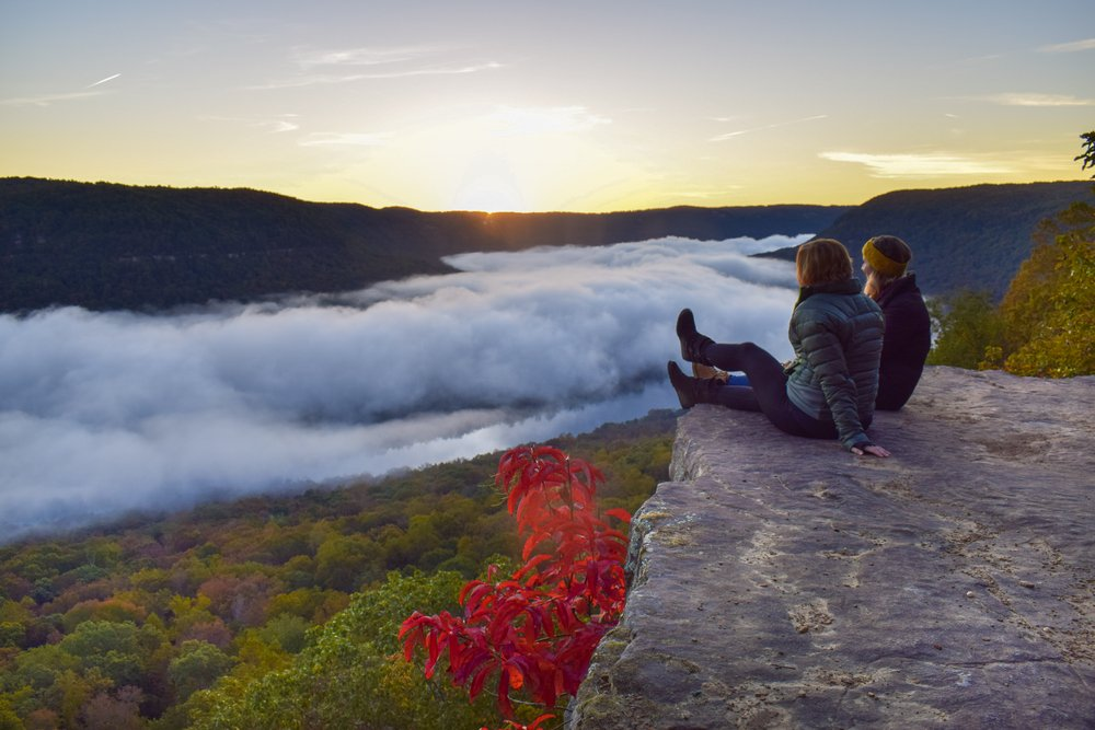 Couple sitting on Sunset Rock in Chattanooga at sunset with fog rolling in the valley below