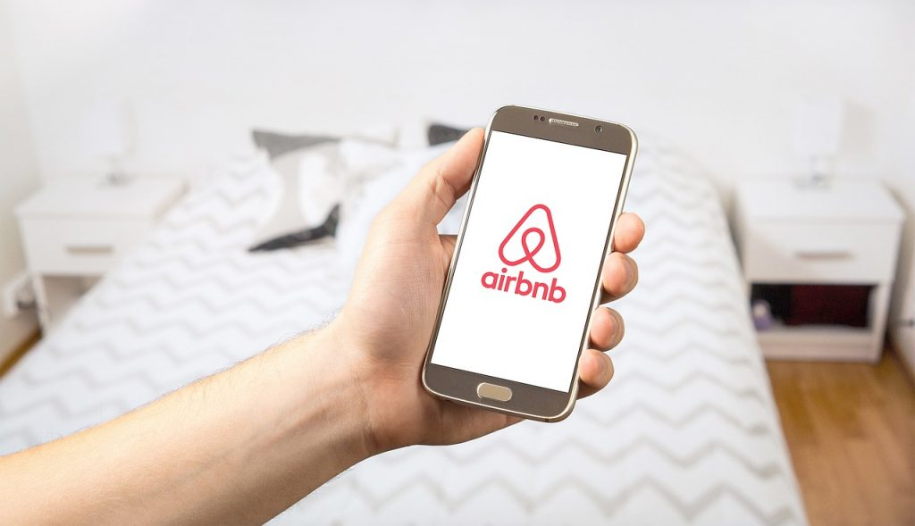cell phone in hand with airbnb logo on screen