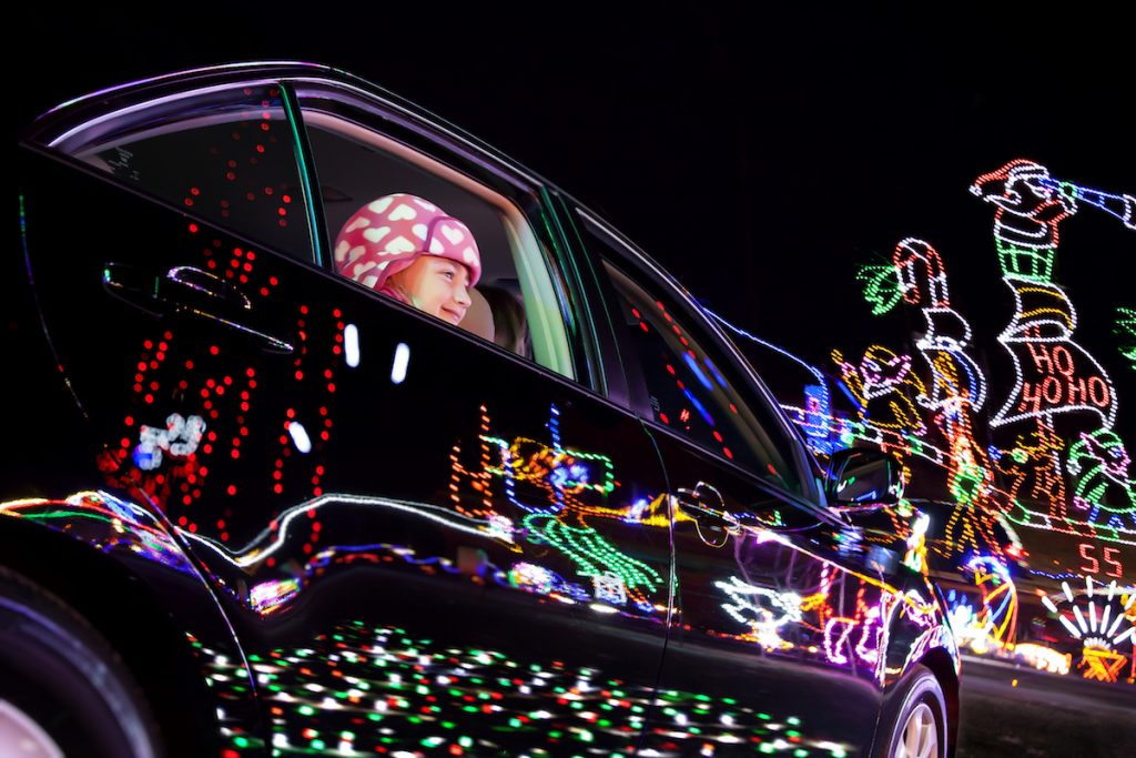 child in car looking at lights during Christmas in the smokies