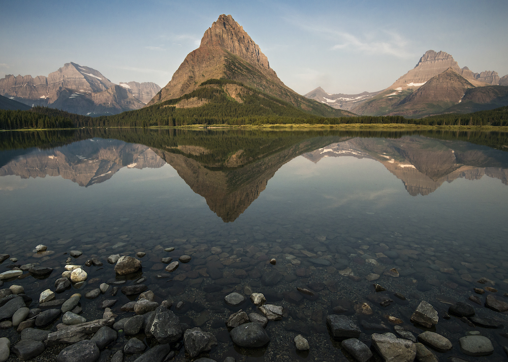 Grinnell Peak is reflected in the still waters of Swiftcurrent Lake at Many Glacier. Mt Gould is to the left and Mt. Wilbur is to the right.